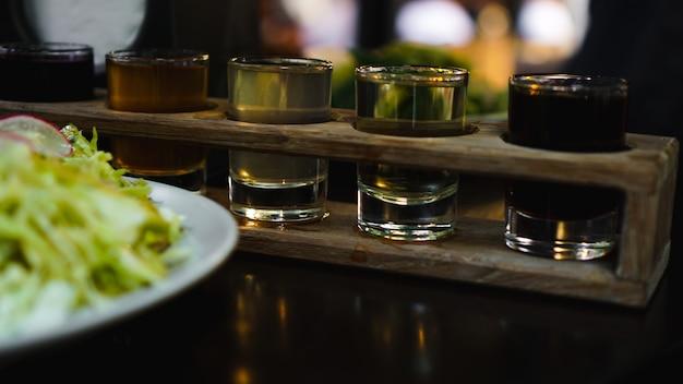 Shot-set in einer reihe, sechs portionen auf einem holzständer und grren-salat. getränk für das menü restaurant, bar, café