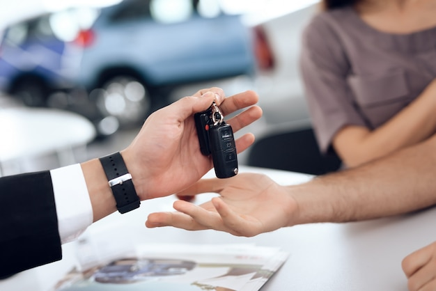 Showroom-händler, der dem käufer die autoschlüssel gibt.