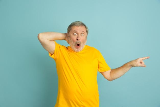 Shpcked zeigt zur seite. kaukasisches mannporträt lokalisiert auf blauem studiohintergrund. schönes männliches modell im gelben hemd, das aufwirft.