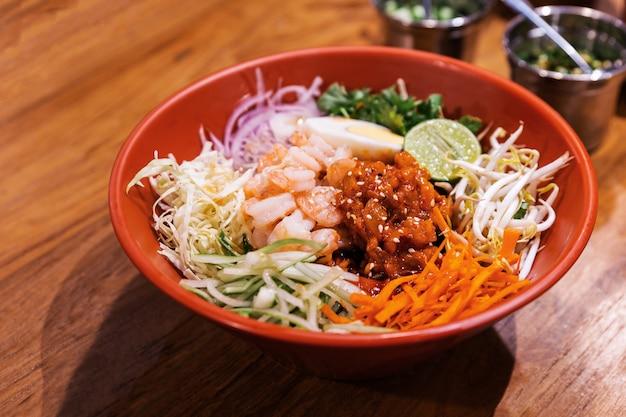 Shrimp bibimbap nudeln, koreanische nudeln gemischt mit radieschen, spross, karotte, kohl, gurke, kochei und gochujang in einer roten schüssel, serviert mit kimchi und roten essstäbchen. perfekte köstliche küche.