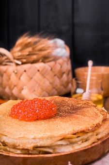 Shrovetide maslenitsa week festivalessen. stapel russischer pfannkuchen mit rotem kaviar. rustikaler stil, freier platz für text,