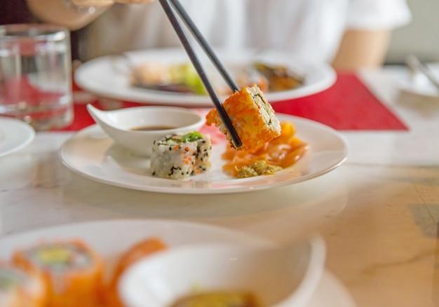 Shushi mit essstäbchen essen, konzentrieren sie sich selektiv