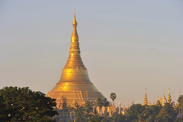 Shwedagon pagode tempel mit dorf unten im morgenlicht in yangon, myanmar (birma)