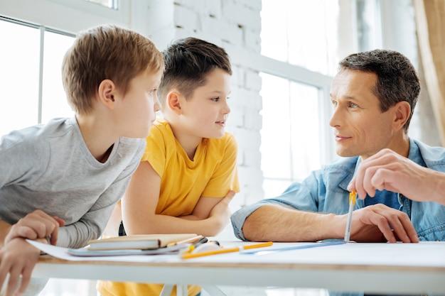 Sich amüsieren. angenehmer junger ingenieur, der an einer blaupause arbeitet, während er mit seinen kindern plaudert, die ihn in seinem büro besuchen