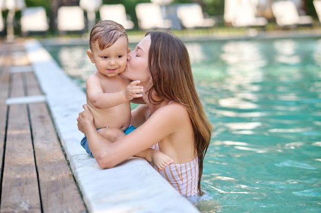 Sich ausruhen. eine junge frau, die ihr kind hält und sich beim schwimmen in einem pool gut fühlt
