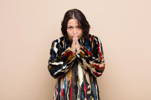 Sich besorgt, hoffnungsvoll und religiös fühlen, treu mit gepressten handflächen beten und um vergebung bitten
