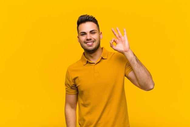 Sich erfolgreich und zufrieden fühlen, mit offenem mund lächeln, mit der hand ein gutes zeichen machen