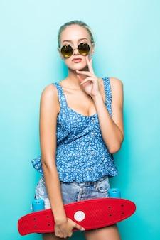 Sich frei und glücklich fühlen. attraktive junge frau in der sonnenbrille, die lächelt und skateboard trägt, während sie gegen blauen hintergrund steht