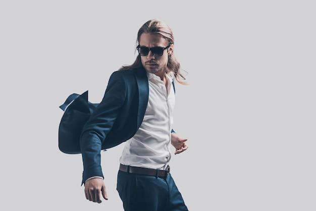 Sich frei und wohl fühlen in seinem stil. hübscher junger mann in vollem anzug und sonnenbrille, der sich vor grauem hintergrund bewegt