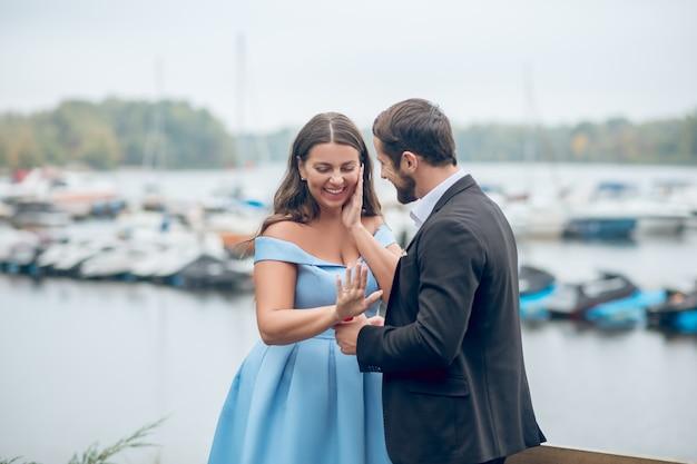 Sich freuende bescheidene frau, die hand und profil des zufriedenen mannes während der verlobung betrachtet