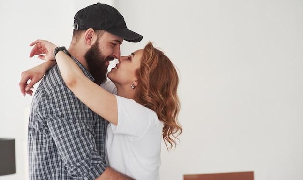 Sich gegenseitig küssen. glückliches paar zusammen in ihrem neuen haus. konzeption des umzugs