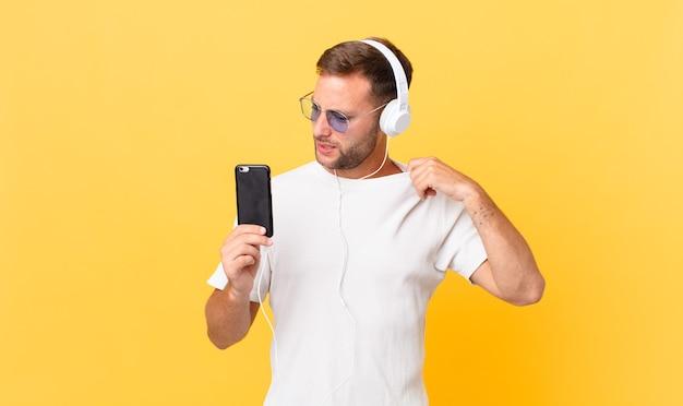 Sich gestresst, ängstlich, müde und frustriert fühlen, musik mit kopfhörern und einem smartphone hören