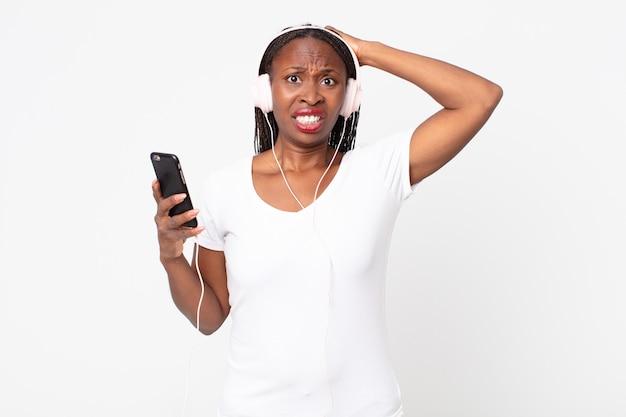 Sich gestresst, ängstlich oder verängstigt fühlen, mit den händen auf dem kopf mit kopfhörern und einem smartphone