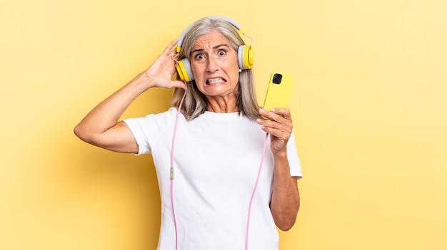 Sich gestresst, besorgt, ängstlich oder verängstigt fühlen, mit den händen auf dem kopf, bei einem fehler mit kopfhörern in panik geraten