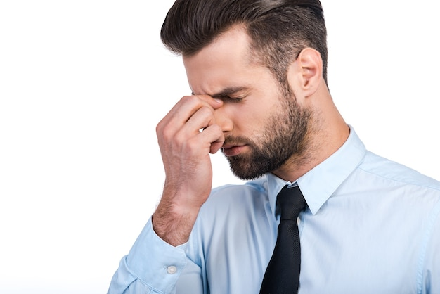 Sich gestresst fühlen. frustrierter junger mann in hemd und krawatte massiert die nase und hält die augen geschlossen, während er vor weißem hintergrund steht