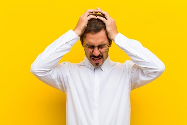 Sich gestresst und frustriert fühlen, die hände zum kopf heben, sich müde, unglücklich und mit migräne fühlen