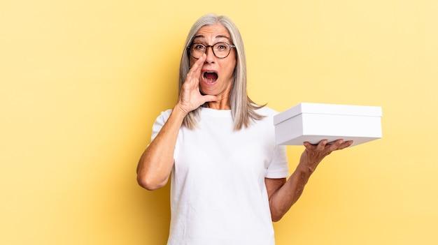 Sich glücklich, aufgeregt und positiv fühlen, mit den händen neben dem mund einen großen schrei aussprechen, rufen und eine weiße box halten