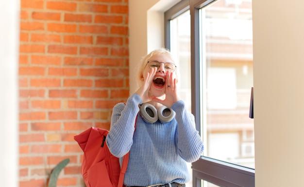 Sich glücklich, aufgeregt und positiv fühlen, mit den händen neben dem mund einen großen schrei aussprechen, schreien