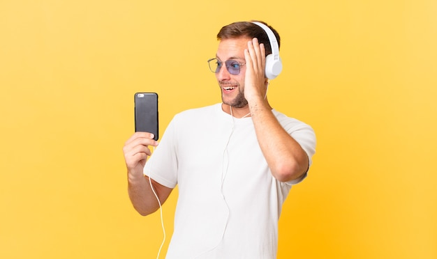 Sich glücklich, aufgeregt und überrascht fühlen, musik mit kopfhörern und einem smartphone hören