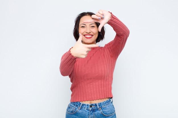 Sich glücklich, freundlich und positiv fühlen, lächeln und mit den händen ein porträt oder einen fotorahmen machen