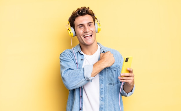 Sich glücklich, positiv und erfolgreich fühlen, motiviert sein, sich einer herausforderung zu stellen oder gute ergebnisse zu feiern. kopfhörer- und smartphone-konzept