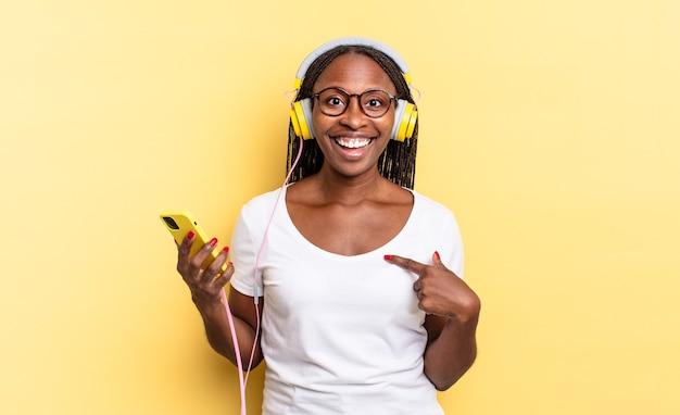 Sich glücklich, überrascht und stolz fühlen, mit einem aufgeregten, erstaunten blick auf sich selbst zeigen und musik hören