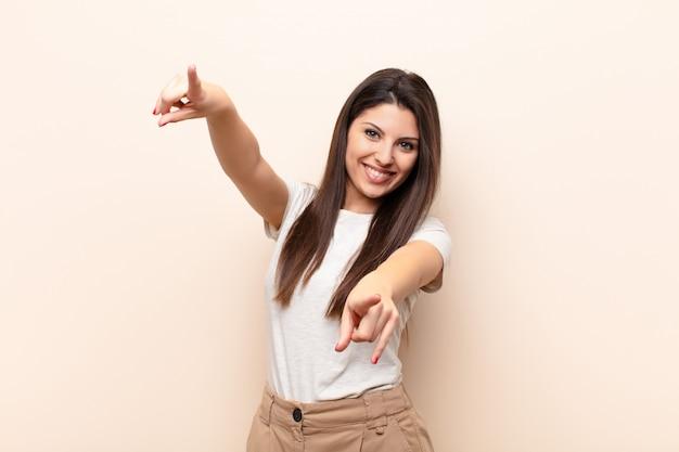 Sich glücklich und selbstsicher fühlen, mit beiden händen zeigen und lachen, dich wählen
