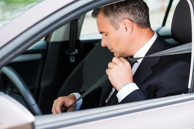 Sich im neuen auto sicher fühlen. selbstbewusster reifer geschäftsmann, der den sicherheitsgurt anlegt, während er in seinem auto sitzt