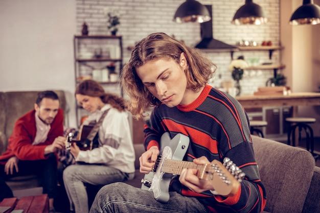 Sich inspiriert fühlen. blonde studentin mit bob-cut-feeling inspiriert wirklich beim gitarrenspiel