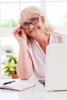 Sich jung und aktiv fühlen. fröhliche ältere frau, die ihre brille justiert und lächelt, während sie am laptop arbeitet