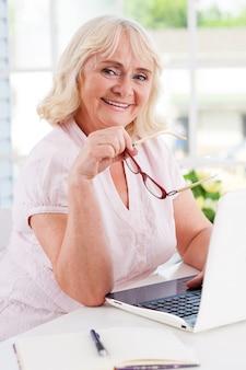 Sich jung und energiegeladen fühlen. glückliche ältere frau, die laptop benutzt und in die kamera lächelt, während sie am tisch sitzt