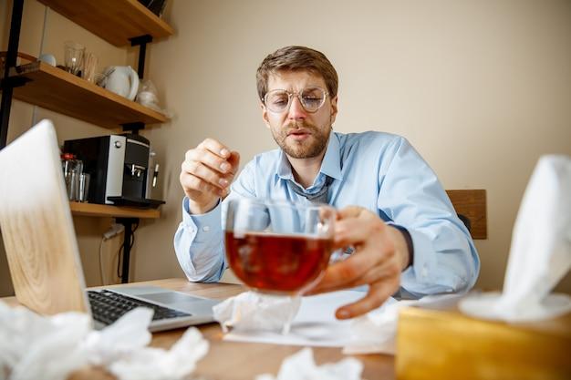 Sich krank und müde fühlen. der mann mit der tasse heißen tees, der im büro arbeitet, fing geschäftsmann kalte, saisonale grippe. influenza-pandemie, krankheitsvorbeugung, klimaanlage im büro verursachen krankheit