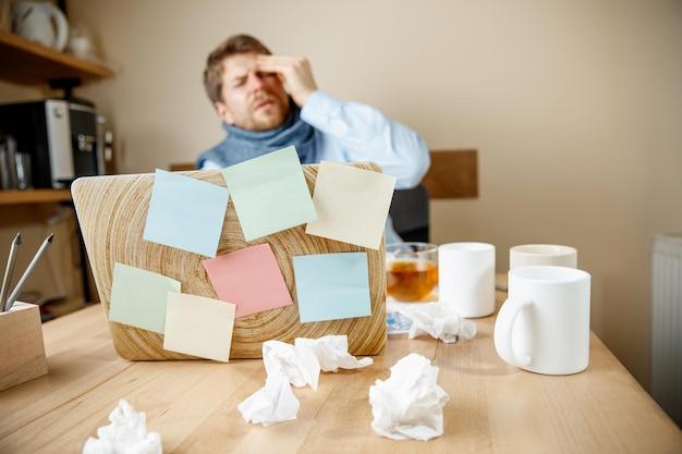 Sich krank und müde fühlen. frustrierter junger mann, der seinen kopf massiert, während er an seinem arbeitsplatz sitzt