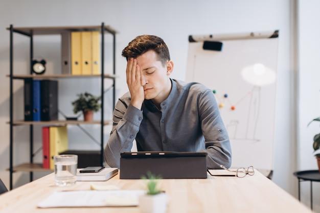 Sich krank und müde fühlen. frustrierter junger mann, der sich die nase massiert und die augen geschlossen hält, während er an seinem arbeitsplatz im büro sitzt