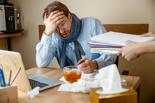 Sich krank und müde fühlen. frustrierter trauriger unglücklicher kranker junger mann, der seinen kopf massiert, während er an seinem arbeitsplatz im büro sitzt. das konzept der saisonalen grippe, der pandemischen influenza und der prävention von krankheiten