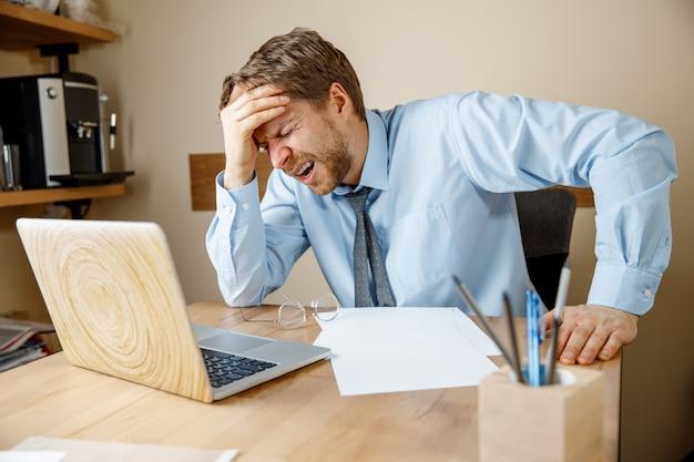 Sich krank und müde fühlen. frustrierter trauriger unglücklicher kranker junger mann, der seinen kopf massiert, während er an seinem arbeitsplatz im büro sitzt.