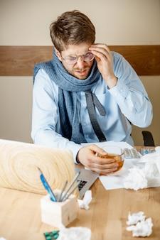 Sich krank und müde fühlen. trauriger unglücklicher kranker junger mann, der seinen kopf massiert, während er an seinem arbeitsplatz im büro sitzt. das konzept der saisonalen grippe, der pandemischen influenza und der prävention von krankheiten