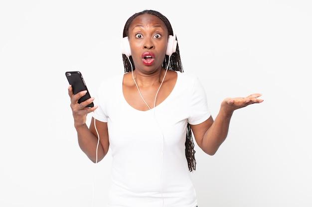 Sich mit kopfhörern und einem smartphone extrem schockiert und überrascht fühlen