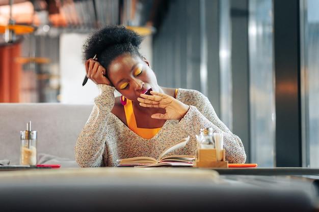Sich müde fühlen intelligenter fleißiger schüler mit gelbem lidschatten, der gähnt, während er sich müde fühlt