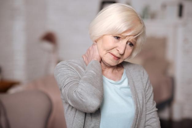 Sich schlecht fühlen. schließen sie herauf porträt der hübschen älteren dame, die ihren schmerzenden hals berührt.