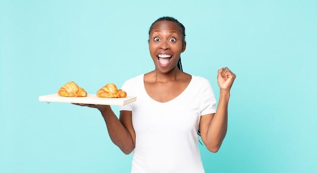 Sich schockiert fühlen, lachen und erfolge feiern und ein croissant-tablett in der hand halten