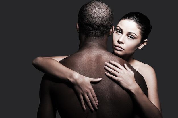 Sich sicher und geschützt fühlen. schöne kaukasische frau, die schwarzen mann umarmt und in die kamera schaut, während beide vor grauem hintergrund stehen
