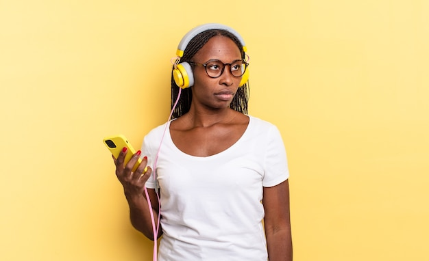 Sich traurig, verärgert oder wütend fühlen und mit einer negativen einstellung zur seite schauen, die stirn runzeln in meinungsverschiedenheiten und musik hören