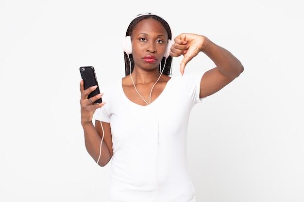 Sich verärgert fühlen, daumen nach unten mit kopfhörern und einem smartphone zeigen