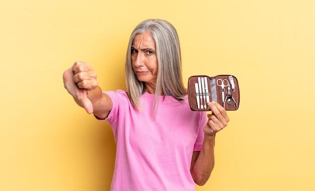 Sich verärgert, wütend, verärgert, enttäuscht oder unzufrieden fühlen, daumen nach unten zeigen mit einem ernsten blick, der einen nagelwerkzeugkoffer hält