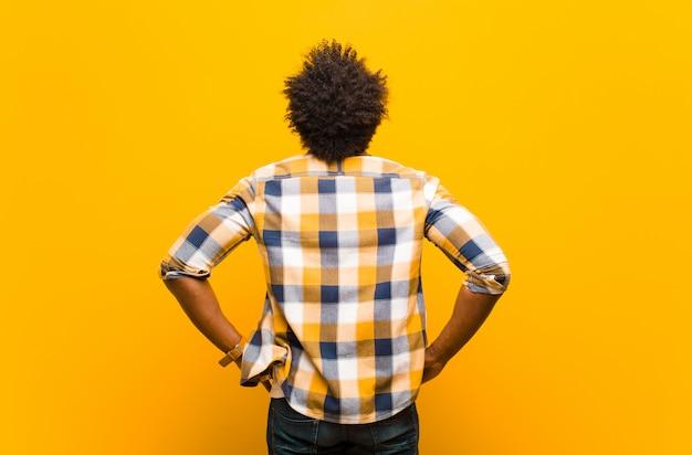 Sich verwirrt oder voll fühlen oder zweifel und fragen, sich wundern, mit den händen in den hüften, rückansicht