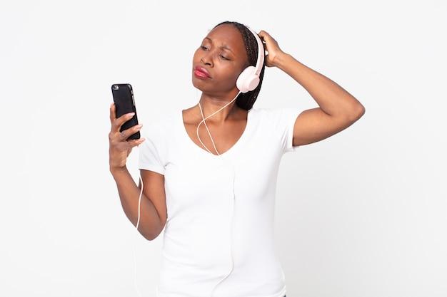 Sich verwirrt und verwirrt fühlen, sich mit kopfhörern und einem smartphone am kopf kratzen