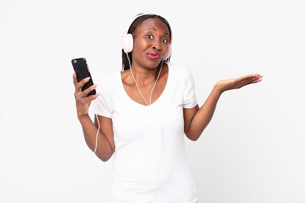 Sich verwirrt und verwirrt fühlen und mit kopfhörern und einem smartphone zweifeln