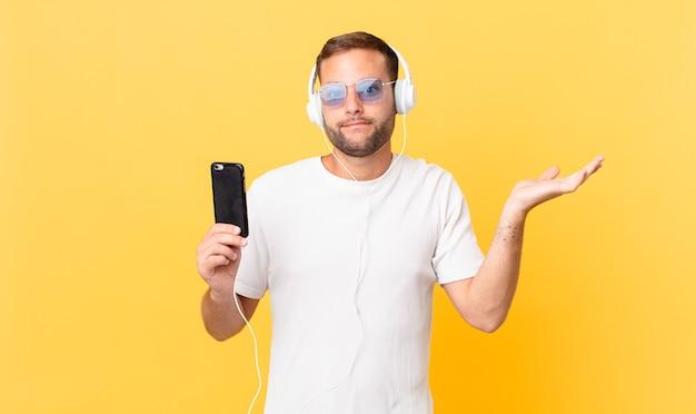 Sich verwirrt und verwirrt fühlen und zweifeln, musik mit kopfhörern und einem smartphone hören