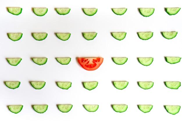 Sich wiederholendes muster aus geschnittenen halbkreisen frischer roher gemüsegurken für salat und eine tomate